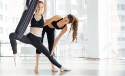 54358521 - happy pretty young woman doing aerial yoga with trainer in studio
