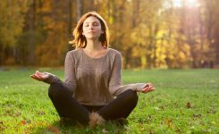 24310492 - beautiful young girl meditating in autumn park